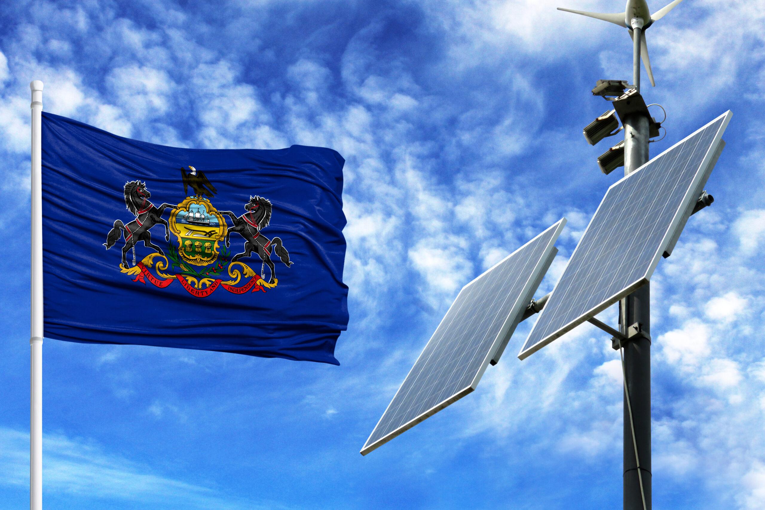 The Pennsylvania State flag waves near a solar panel.