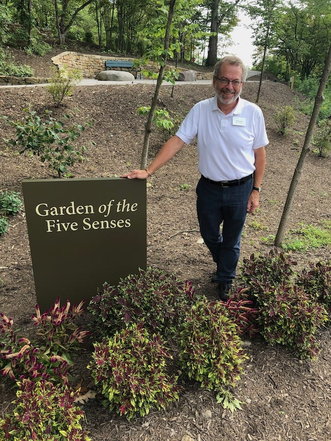 """A man in a white shirt and jeans stands in front of a sign that reads """"Garden of the Five Senses."""""""