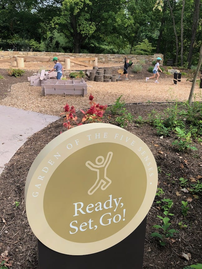 """Children play in a garden behind a sign that reads """"Ready, Set, Go!"""""""
