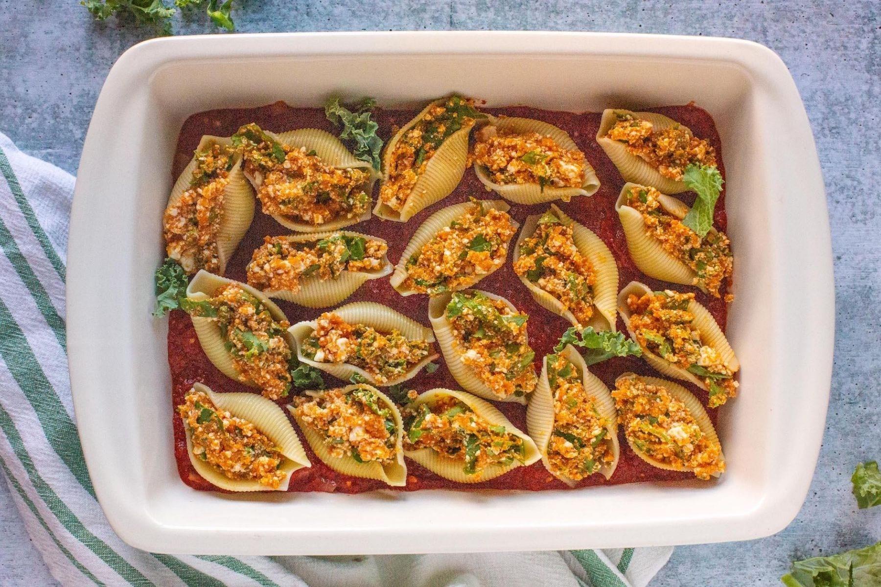 Vegan pumpkin kale stuffed shells in a white baking dish on a grey countertop