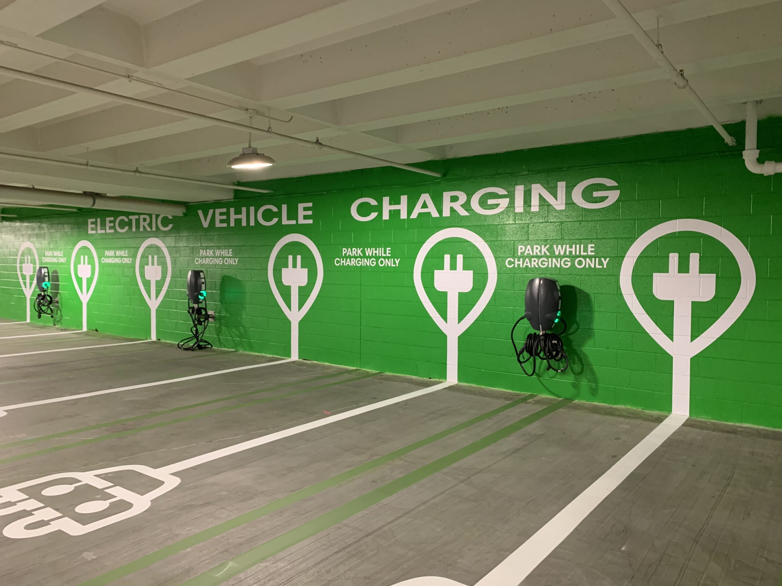The wall of a parking garage is painted green to show that it is an electric charging station.