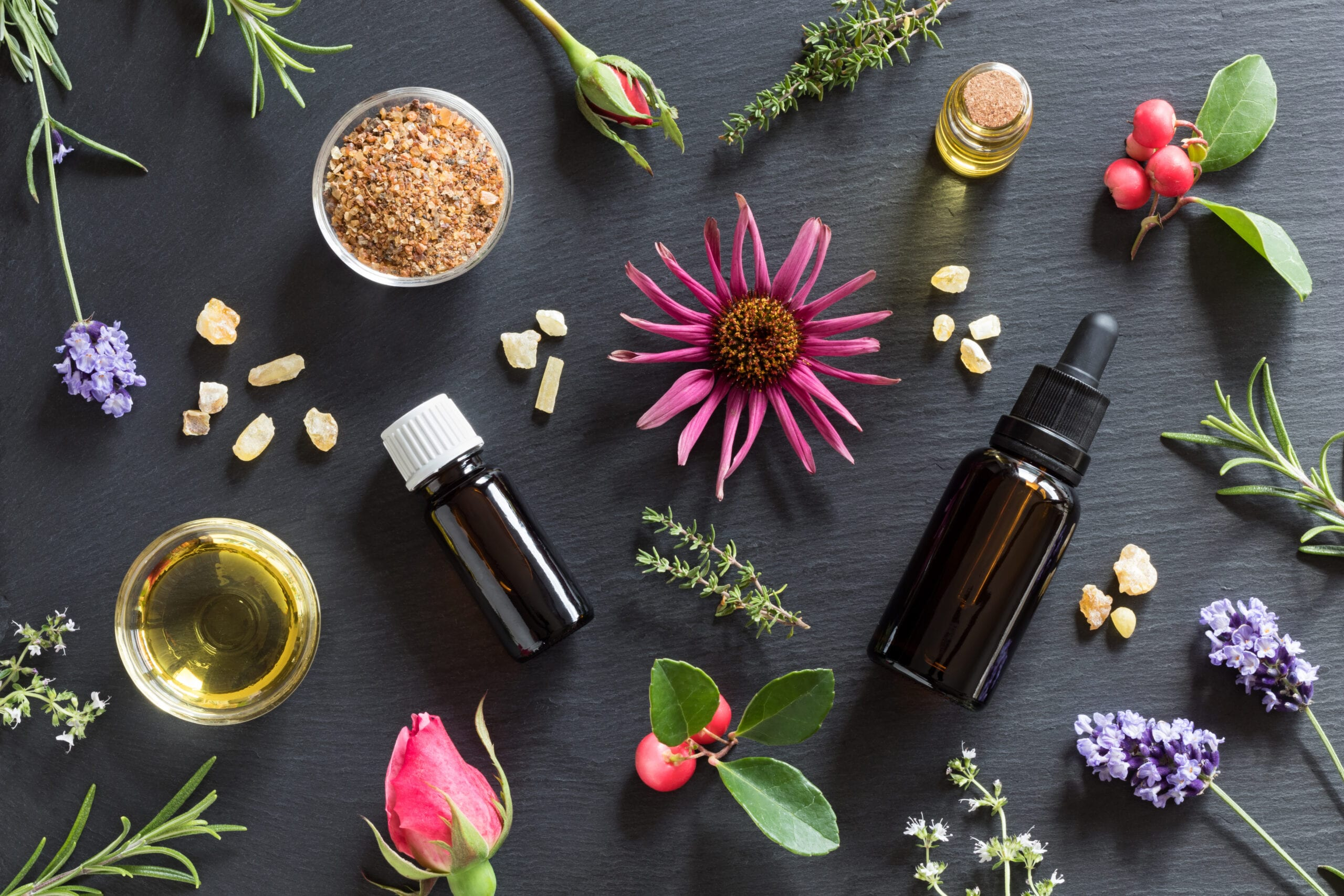 Daisies, roses, lavender, and sprigs of herbs lie on a dark wooden background with glass essential oil containers. Some have a dropper lid, some have a white top