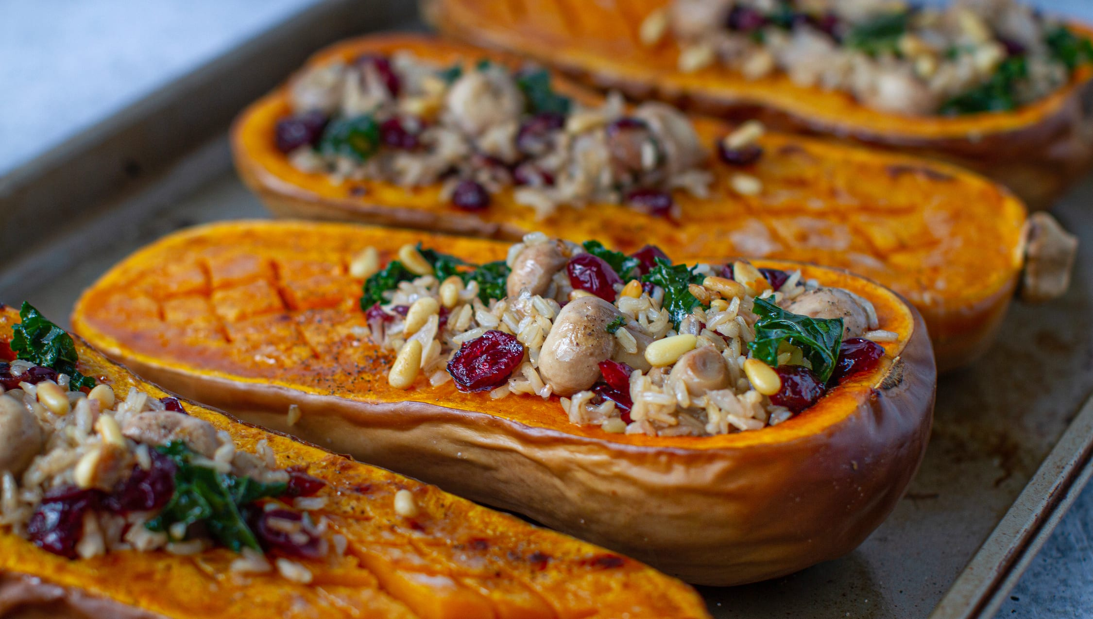 Large, orange roasted butternut squash halves are stuffed with a tasty brown rice, mushroom, cranberry and kale medley make for a perfect vegan fall entree.