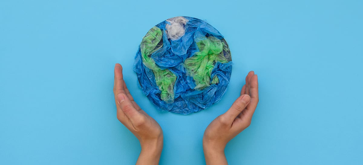 Two hands cradle a small globe made out of green and blue plastic bags.