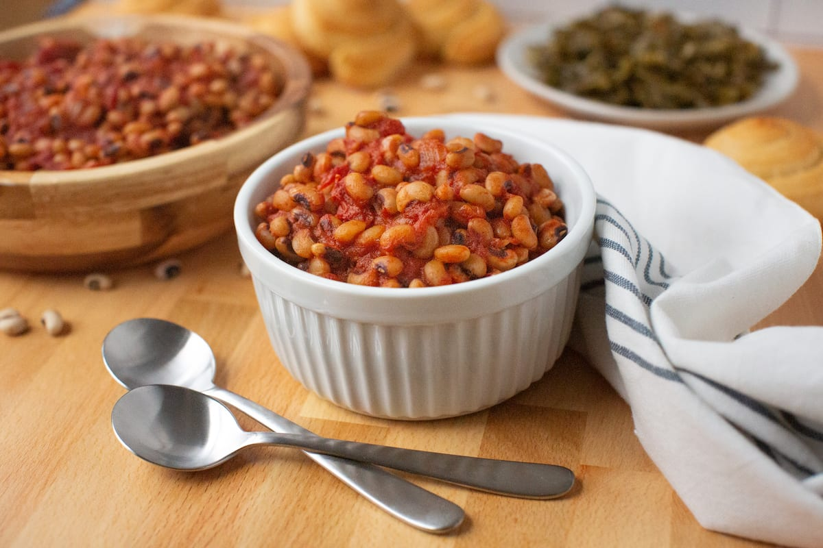 A single-serving bowl of black-eyed peas sits with a larger serving bowl of black-eyed peans, cornbread rolls, and a plate of collard greens.
