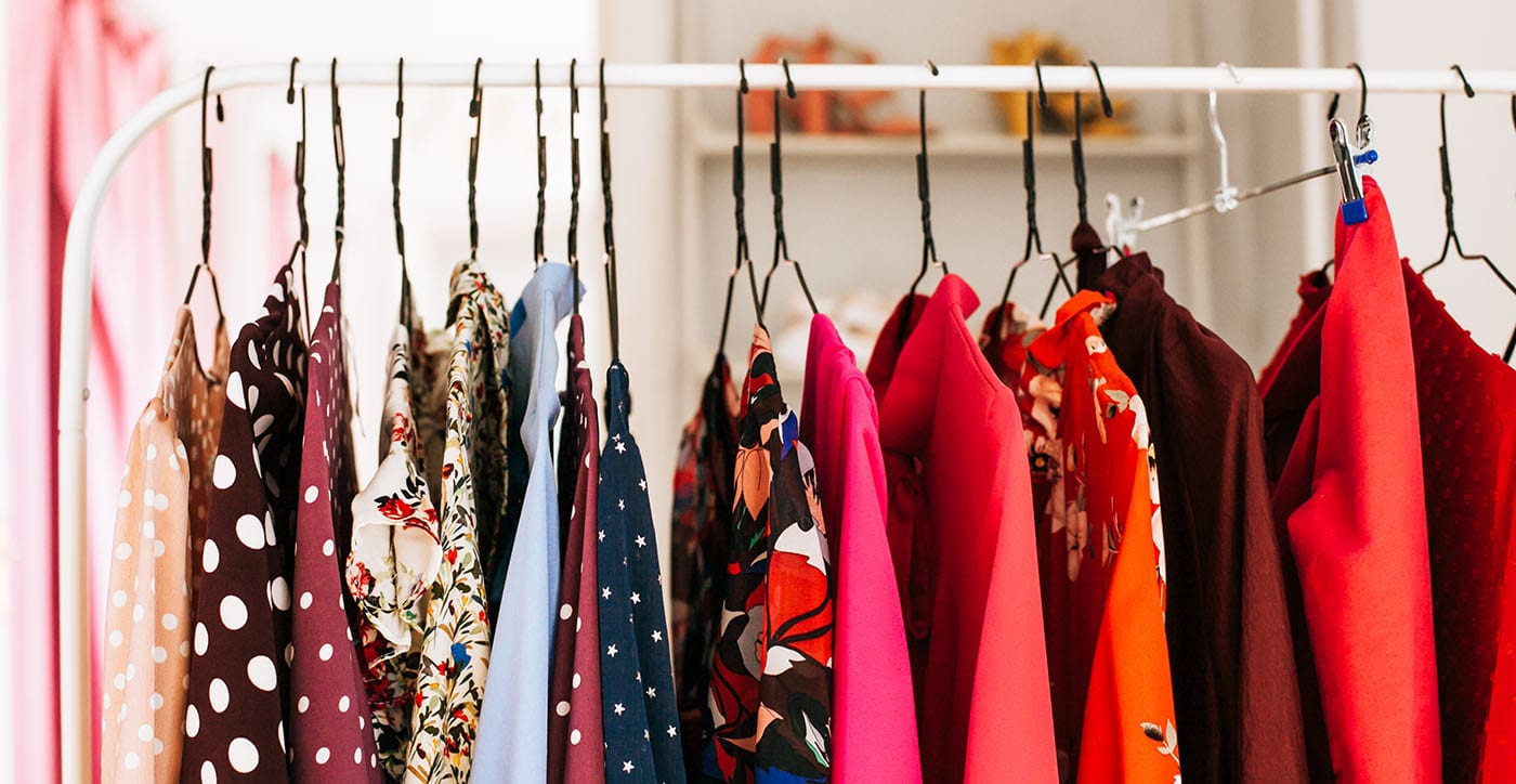 Women's blouses in various textures hang on a clothing rack.