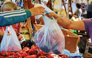 In a busy outdoor market, one person takes a plastic bag full of fruits and vegetables from the seller.