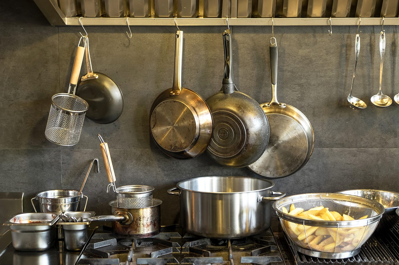 Several large stainless-steel pots and pans rest on top of a stove. Above them are smaller stainless-steel pans and colanders.