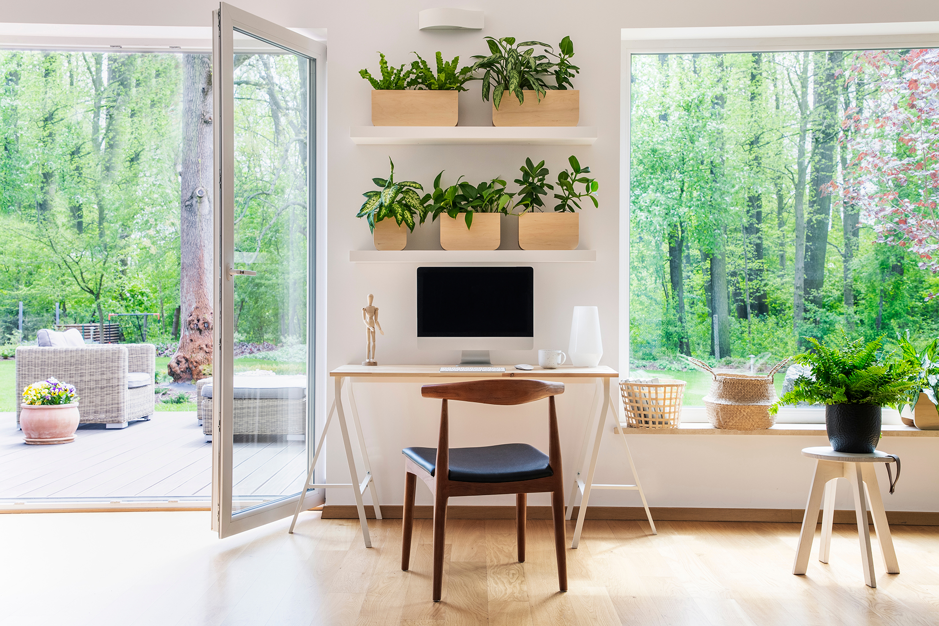 In the center of a bright, airy room is a computer. Above the computer are big shelves full of potted plants. To the left of the computer is a wide-open glass door leading to a beautiful green patio. To the right, are huge windows with views of the backyard and trees.