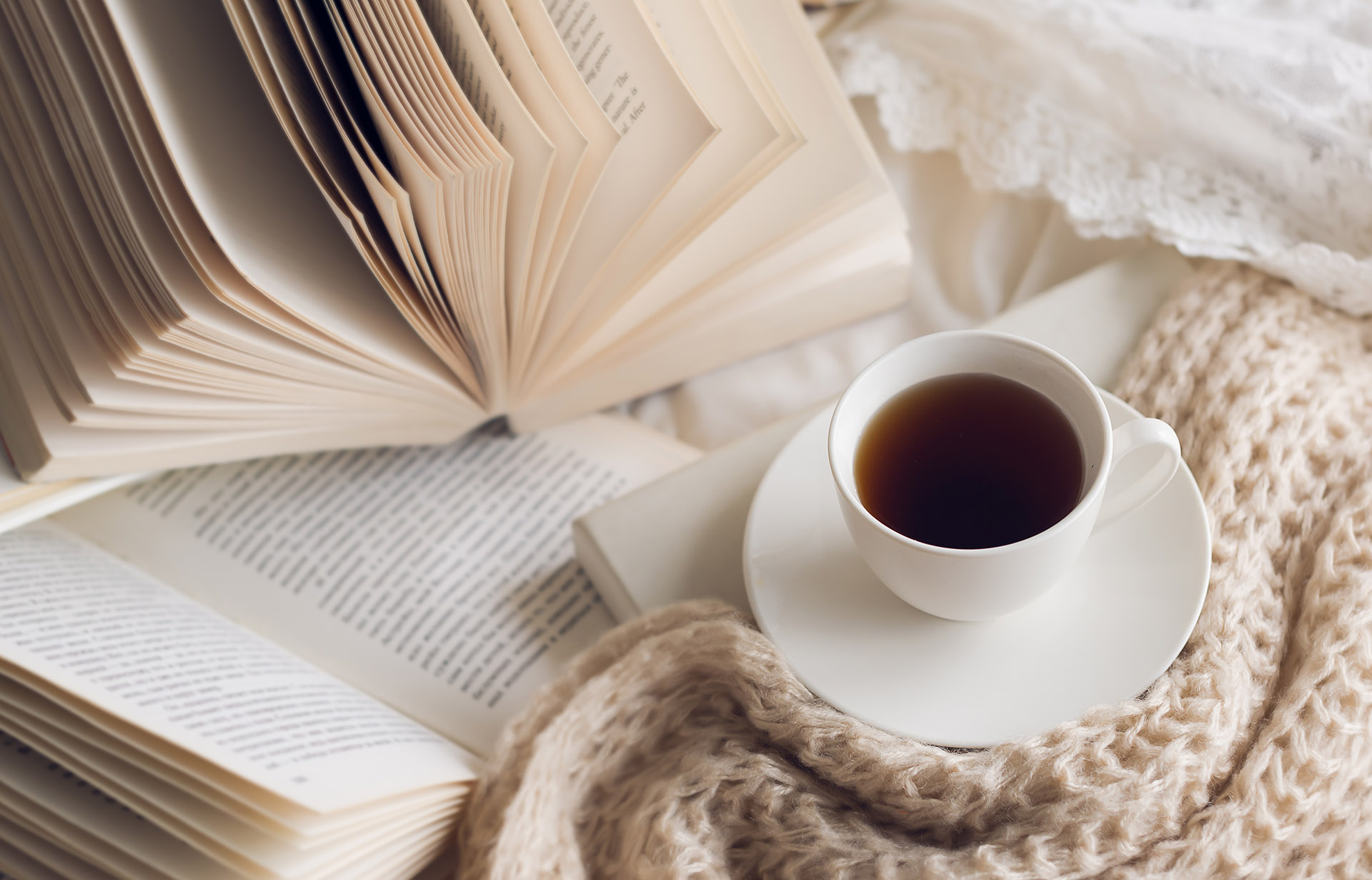 Several books are open on a white bed. Next to the book is a cup of coffee, and oatmeal-colored knit blankets.