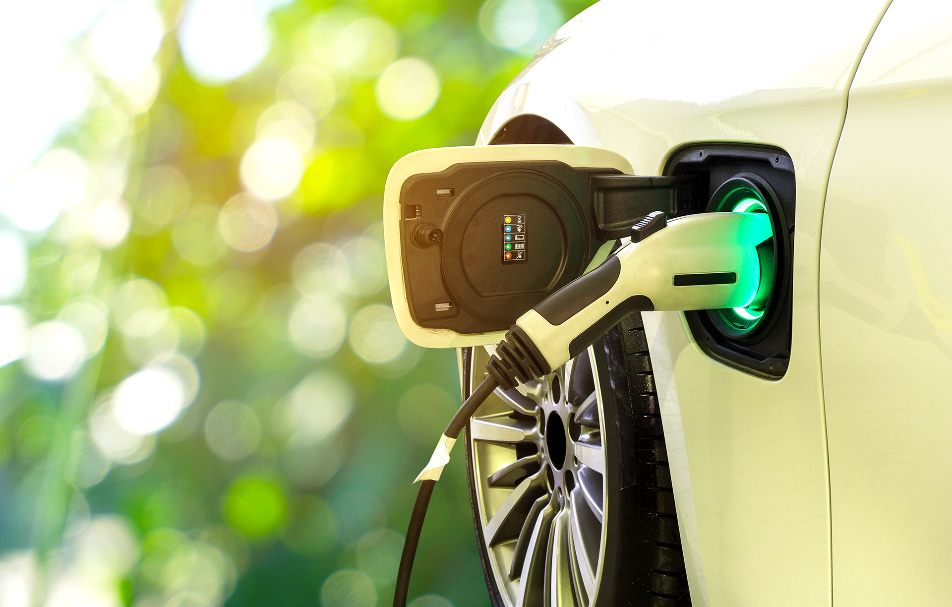 An electric vehicle is at a charging station. The power supply cable is plugged in. The background is blurred leaves with a soft yellow light peeking through.